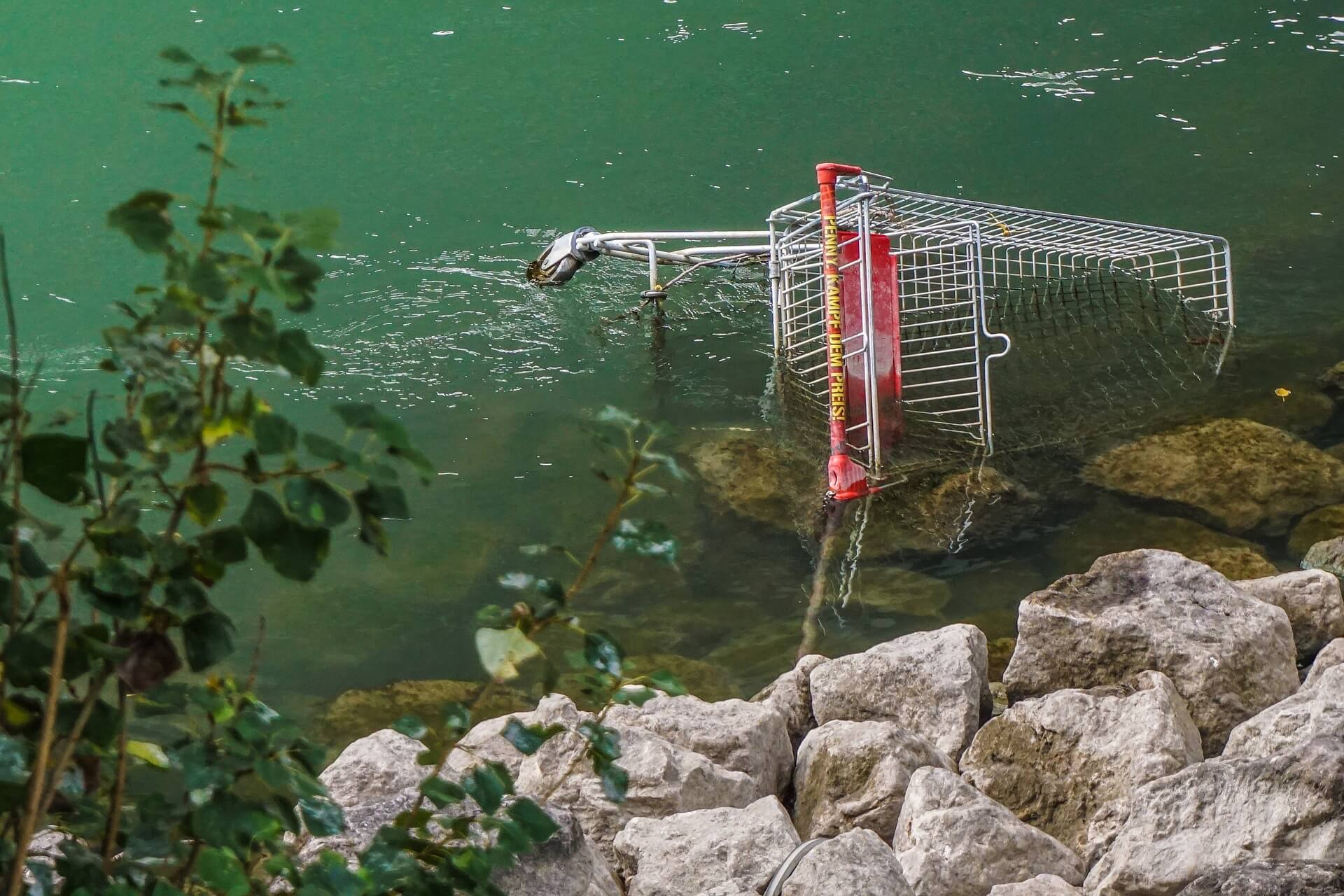 shopping basket lying half submerged in a littered waterway